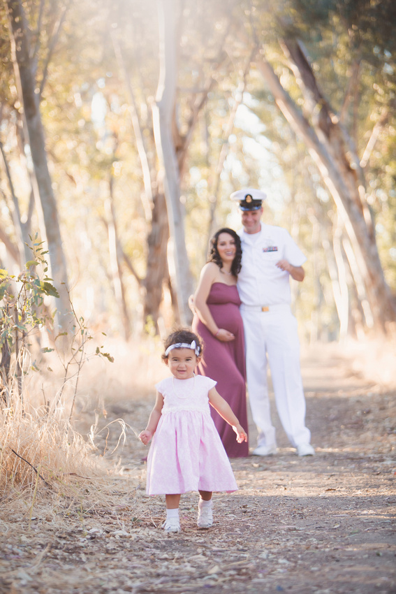 A family portrait with a pregnant momma and her husband in navy uniform with their daughter.
